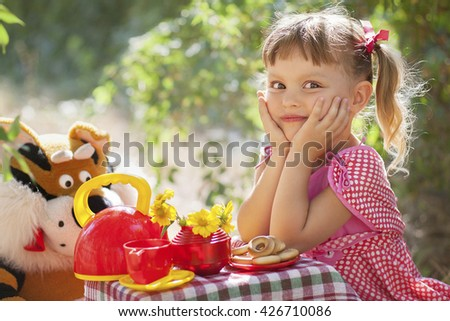 pretty little girl drinks tea with her toy friend in garden - stock photo