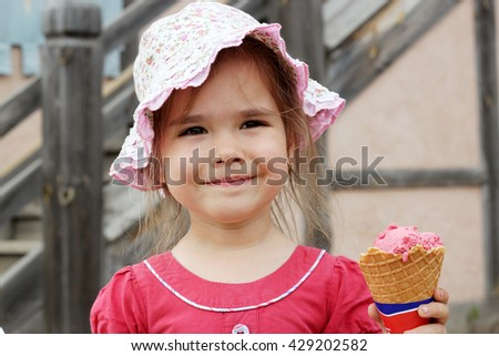 Pretty little girl eating an ice-cream in the park, summer outdoor portrait - stock photo