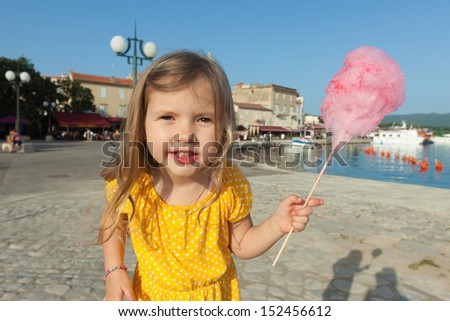 Pretty little girl eating candy floss - stock photo