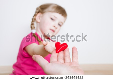 Pretty little girl giving a red heart to her father - stock photo
