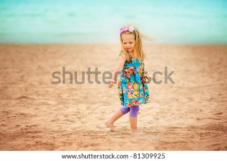 pretty little girl have a fun on sandy beach background - stock photo