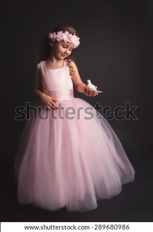 Pretty little girl holding little bird in hands  - stock photo