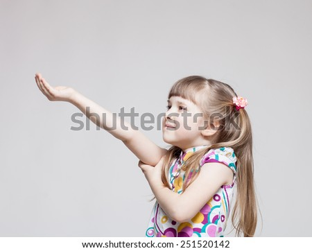 Pretty little girl holding something on neutral background - stock photo