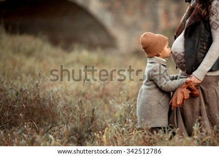 pretty little girl in brown hat and coat standing in the meadow in the park and kiss stomach of her pregnant mother at autumn  - stock photo