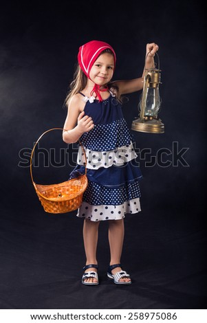 Pretty little girl in dress and red scarf standing with basket and oil-lamp on dark background - stock photo