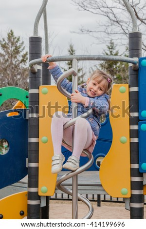 Pretty little girl in jacket, dress and tights playing on children playground, ready to slide fire pole. Warm spring weather. - stock photo
