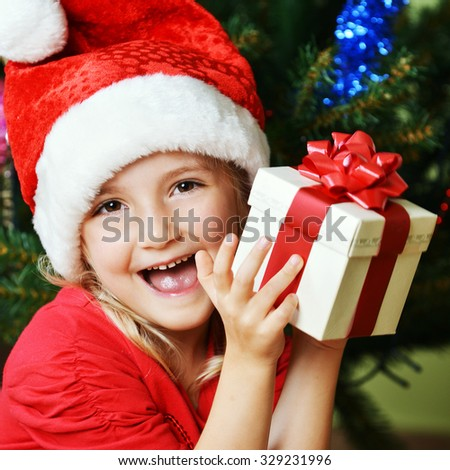 Pretty little girl  in santa cap near Christmas tree - stock photo