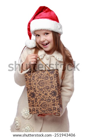 Pretty little girl in Santa's hat holding her Christmas present - stock photo