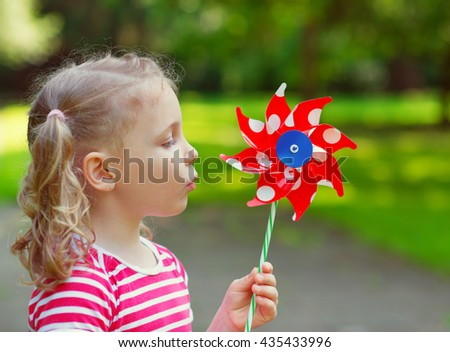 Pretty little girl in summer day holds windmill in hand