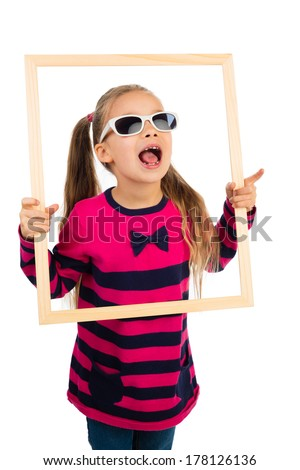 Pretty little girl in sunglasses looking through empty wooden frame, making funny face expression, isolated - stock photo
