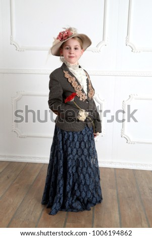 Pretty little girl in vintage dress and retro hat with red flower in hand - full height indoor portrait
