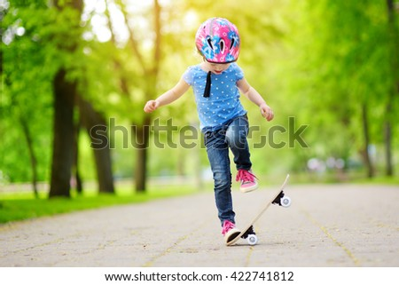 Pretty little girl learning to skateboard outdoors on beautiful summer day - stock photo