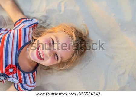 Pretty little girl lies on beach sand and laughs. - stock photo