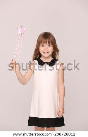 Pretty little girl lokking so brightness. Future model in white dress with long brown hair posing on grey background.