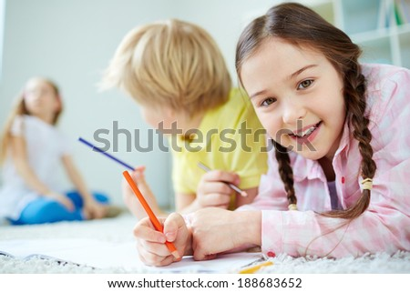 Pretty little girl looking at camera while lying on the floor and drawing with her friends behind - stock photo