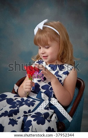 Pretty little girl looking at wild flowers with blue background. - stock photo