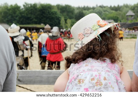Pretty little girl looking on the medieval knights performance during historical festival, theatrical performances involving the troubadours, knights - stock photo