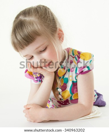 Pretty little girl lying on the floor and looking on her drawing, white background - stock photo
