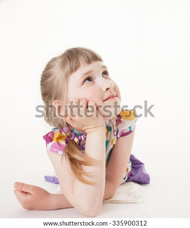 Pretty little girl lying on the floor and thinking, white backround - stock photo