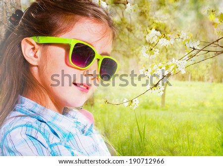 Pretty little girl playing a guitar. Spring time