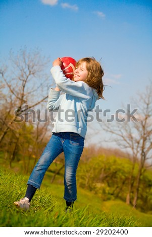Pretty little girl playing with ball on green grass - stock photo