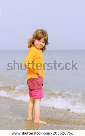 Pretty little girl portrait on the beach looking at camera and smile