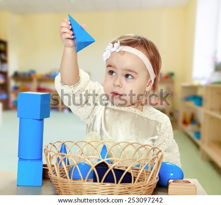 pretty little girl puts cubes Montessori classroom. - stock photo