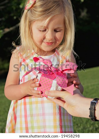 pretty little girl receiving a gift outdoors - stock photo