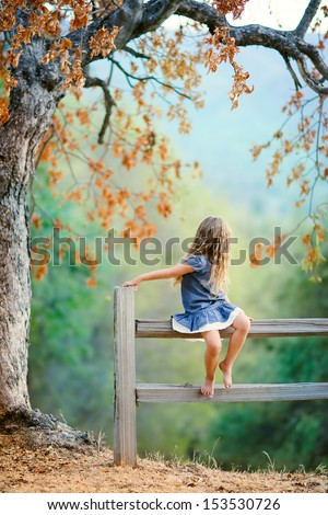 Pretty little girl relax at beauty autumn landscape background - stock photo