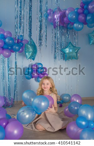 Pretty little girl sits in a studio with a lot of color balloons - stock photo