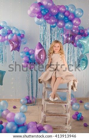 Pretty little girl sits on a stairs in a studio with a lot of color balloons - stock photo