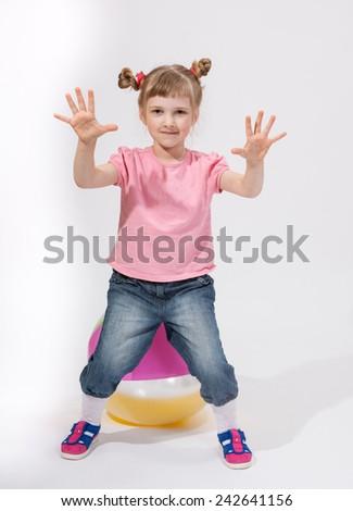 Pretty little girl sitting on a beautiful ball - studio shot - stock photo