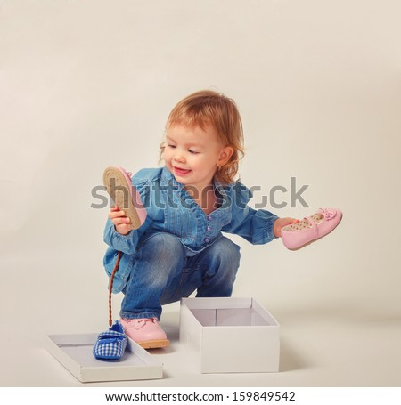 Pretty little girl sitting on the floor, taking on pink shoes - stock photo