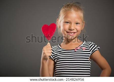 Pretty little girl smiling and posing with lollipop. Studio shutting. Grey background. Looking at camera.