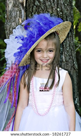 Pretty little girl smiling pretty for her birthday dress up party portrait. - stock photo