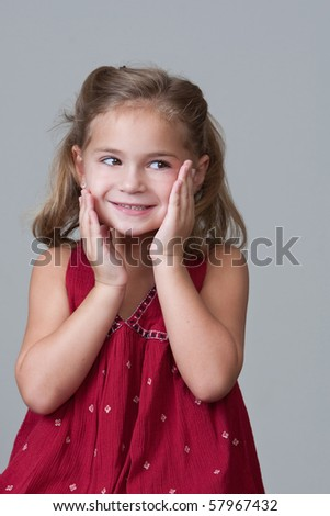 Pretty Little girl smiling with hands to face after being caught doing a mischievous deed. - stock photo