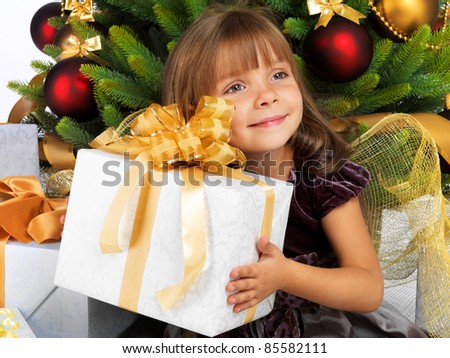 Pretty little girl smiling with present near the Cristmas tree - stock photo