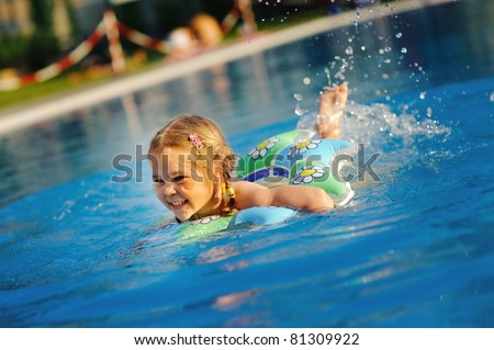 Pretty little girl swimming in outdoor pool and have a fun - stock photo