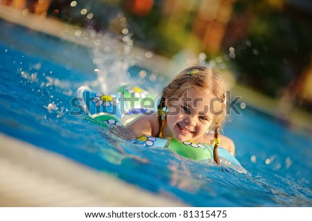 Pretty little girl swimming in outdoor pool and have a fun with a splash - stock photo