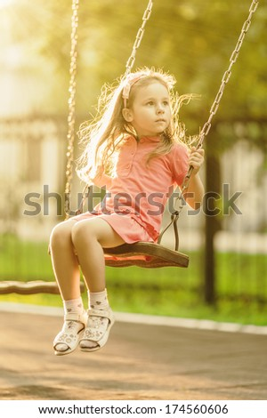 Pretty little girl swinging on seesaw beneath bright shining in summertime - stock photo