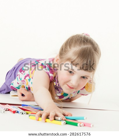 Pretty little girl taking many felt-tip pens, white background