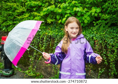 Pretty little girl under the rain, wearing purple rain coat, holding umbrella - stock photo