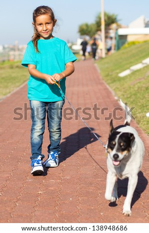 pretty little girl walking a dog outdoors - stock photo
