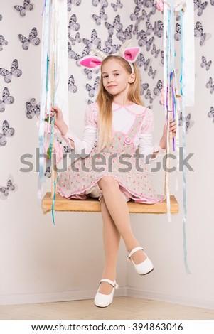 Pretty little girl wearing goat costume posing on the swing - stock photo