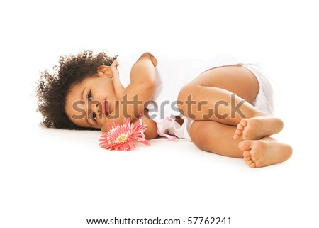 Pretty little girl with a flower laying on white - stock photo