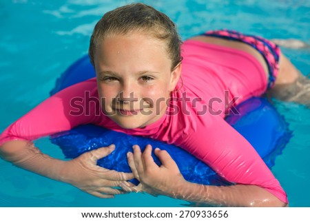 Pretty little girl  with blue life ring has fun in the swimming pool - stock photo