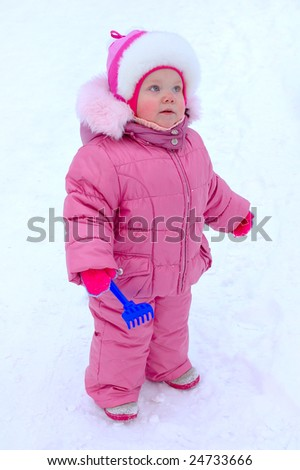 Pretty little girl with blue plastic toy rake in winter outerwear stay on snow-covered ground.