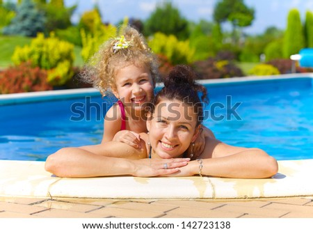 Pretty little girl with her mother in swimming pool outdoors