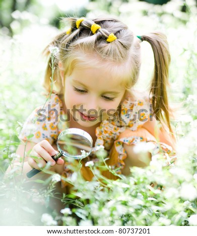 pretty little girl with magnifying glass looks at flower - stock photo