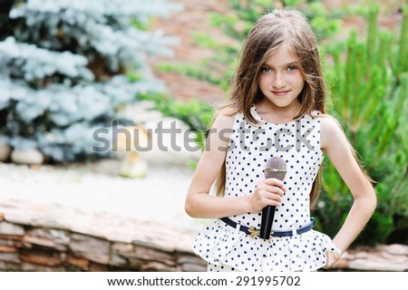 pretty little girl with the microphone in her hands - outdoor - stock photo